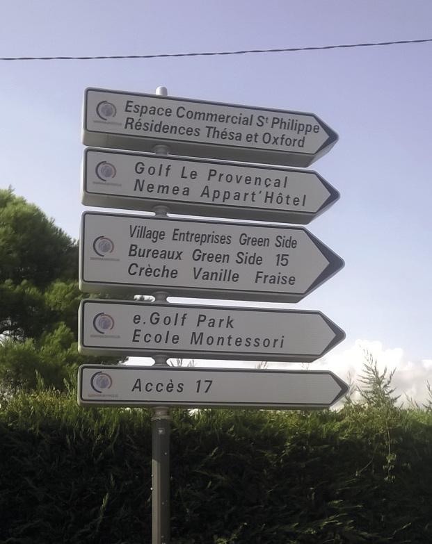 """En route vers la start-up nation. Panneau de signalisation: """"Village entreprise Green Side""""; """"e. Golf Park""""; """"École Montessori""""; etc."""